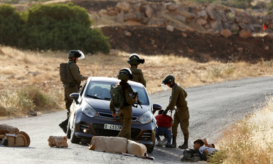 Four soldiers detain youths lying on the street next to a car
