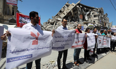 A group of people stand with placards beside a destroyed building