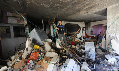 A man stands in a severely damaged building