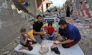 Two adults and two children eat a meal amid buildings that have been destroyed