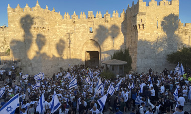 Large group of people with flags against backdrop of ancient stone wall