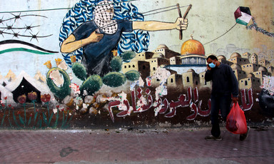 A man with a shopping bag walks past graffiti depicting the Dome of the Rock and keffiyeh-clad youth wielding a slingshot
