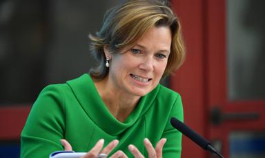 Woman sits behind microphone
