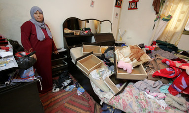 Woman stands next to bed piled up with dresser drawers, blankets and clothing