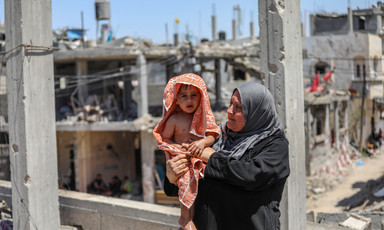 Woman seen from waist up holds a toddler wrapped in a towel while standing in front of bombed-out buildings