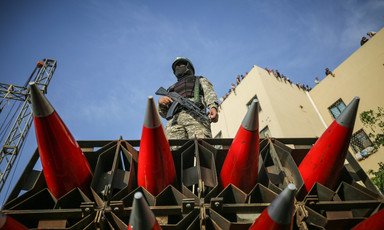 Man stands on truck carrying missiles as people watch from building