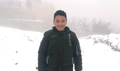 A boy wearing a coat stands in the snow