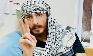 A man in a keffiyeh makes a V for victory sign with his hand