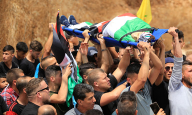 Men carry the body of a boy wrapped in a flag on a stretcher