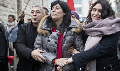 A woman is flanked by a man and a woman