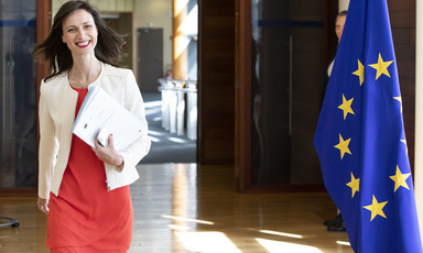 Woman smiles as she carries a dossier