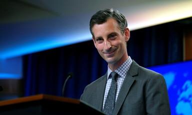 Man at podium smiles