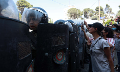Protesters stand beside police in full riot gear