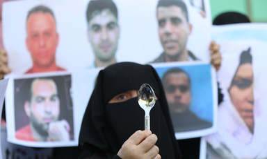 A woman standing by pictures of escaped men holds a spoon