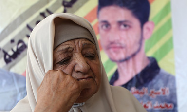 A woman rests her face on her fist with a poster of a man behind her