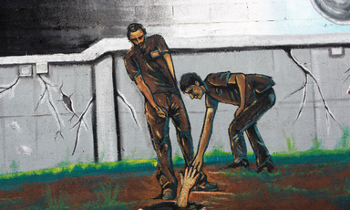 Mural depicts two men reaching out for a hand in a hole in the ground