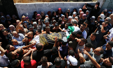 Crowd carries a body wrapped in an Islamic Jihad flag