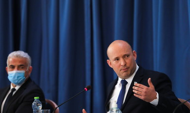Naftali Bennet gestures with hand while sitting at table as Yair Lapid looks on.