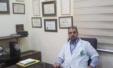Man in medical uniform sits at desk with framed diplomas on wall behind him