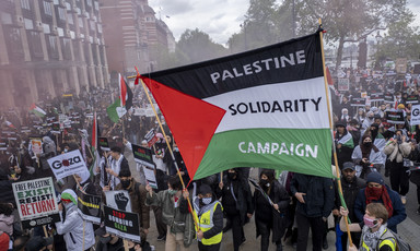 """A flag banner in a crowd of people reads """"Palestine Solidarity Campaign"""""""
