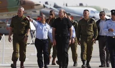 A group of men in uniforms walk in front of warplanes