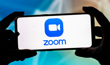 Fingers hold a smartphone displaying Zoom logo