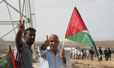 Two men with Palestinian flag make victory sign