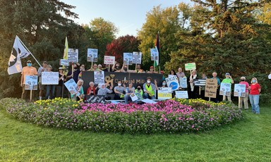 Protesters with signs pose for group photo at General Mills campus