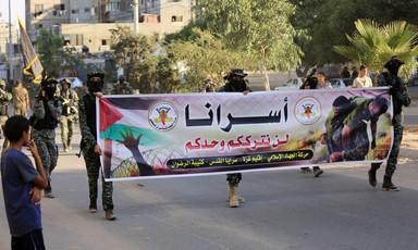 Men dressed in military uniform hold banner