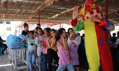 Children play behind a clown