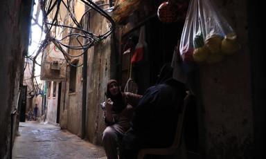 Two women sit outside a shop