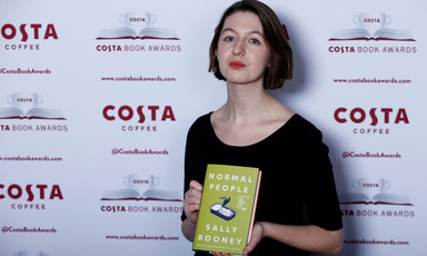 Woman holds a copy of a book