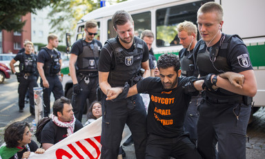 "A man wearing a ""boycott Israeli apartheid"" T-shirt is grabbed by two German police officers."